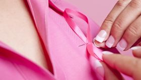 Woman pinning pink ribbon on her blouse.