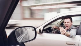 Man in car gesticulating angrily at another driver (blurred motion)