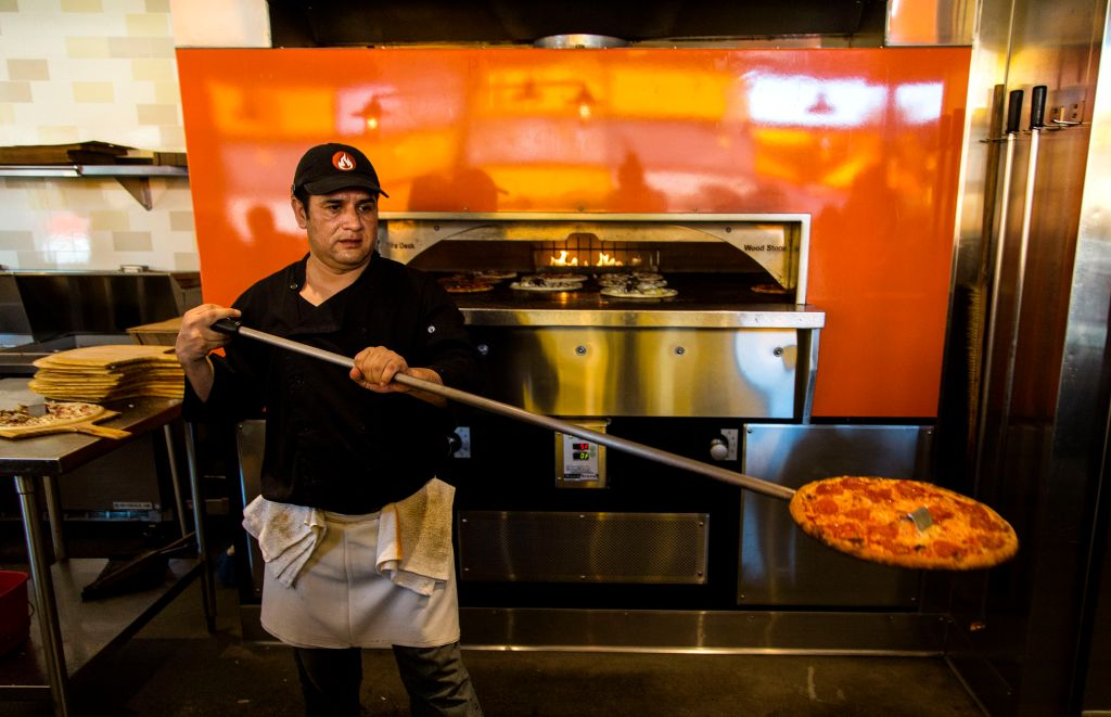 PASADENA, CA - FEBRUARY 21, 2014 - Pizza cook Jorge Agundez, cq, taking a pizza out of the oven at B