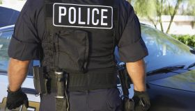 Police officer in bulletproof vest outdoors, back view