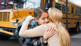 Girl and mother hugging by school bus