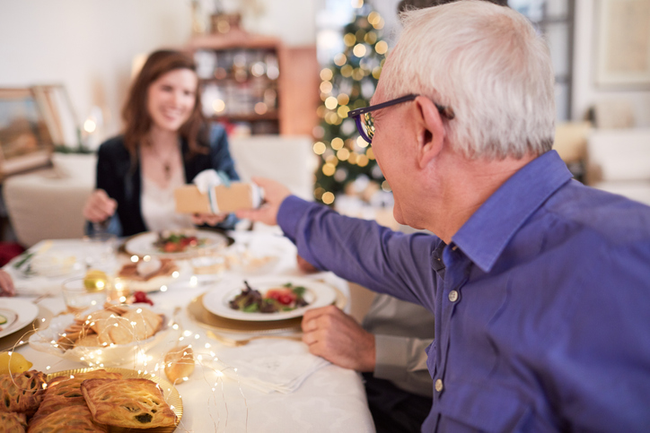Father giving a gift to her daughter at the Christmas table.