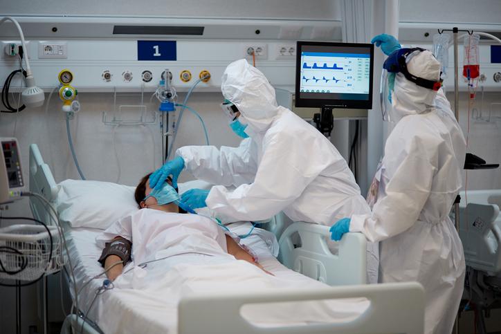 Medical Worker Adjusting Female Patient Oxygen Mask