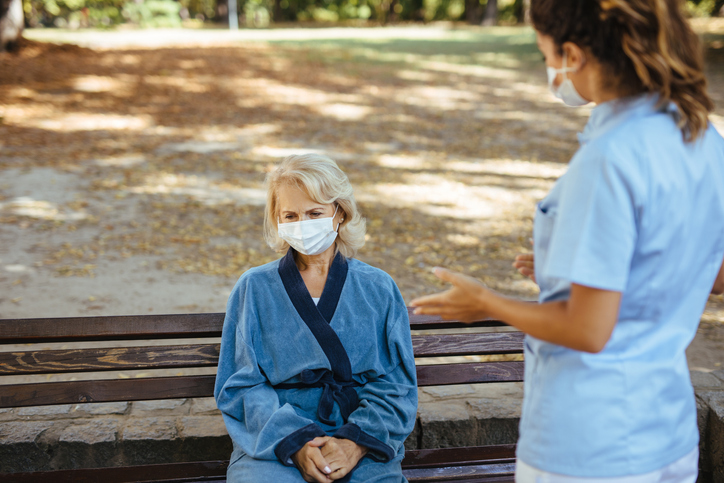 Elderly woman with protective face masks on sitting on a bench and talking to healthcare worker at nursing home