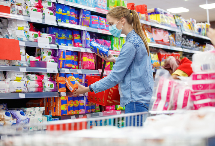 Woman choosing between two brands of sanitary napkins or tampons during coronavirus outbreak